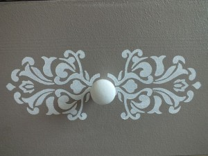 Motif au pochoir blanc sur fond taupe autour du bouton Photo Pinterest : Enregistré par Beatrice Denis